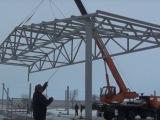 Подъем краном будущей крыши здания из металлоконструкций